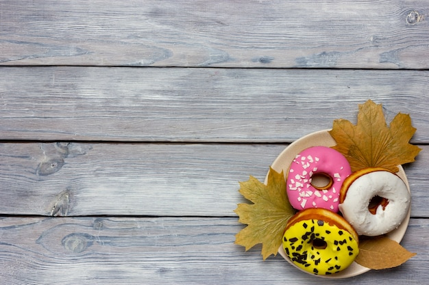 Colored donuts that lie on an autumn yellow maple leaf on a wooden table top view