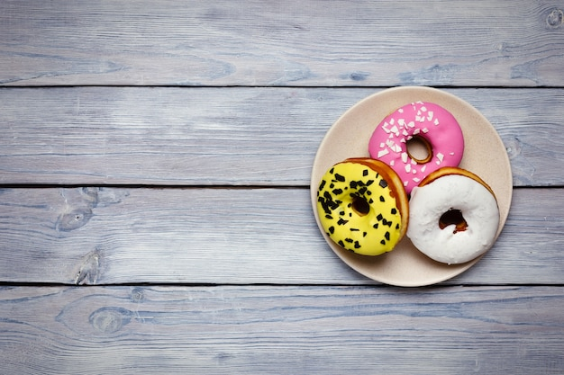 Colored donuts on wooden background top view