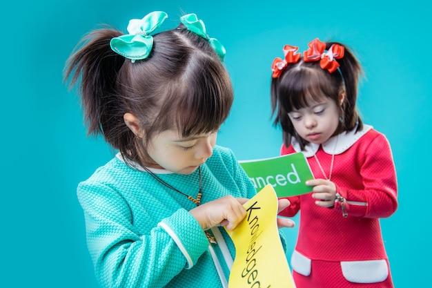 色付きのドレス。青い壁に立って言葉でポスターを観察する好奇心旺盛な若い女性