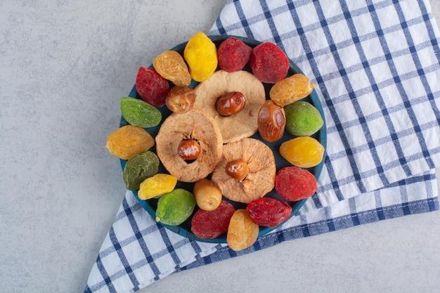 Ciliegie secche colorate e frutta sulla superficie del cemento.