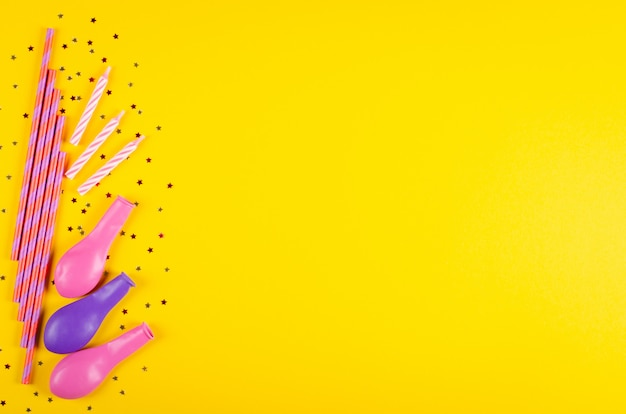 Colored drinking straws and air balloons composition on yellow background, party and celebration decoration.