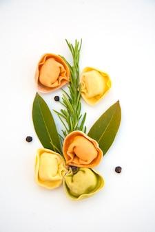 明るい表面に色付きの餃子とスパイス。イタリア料理、ハーブ入り未調理のラビオリ、分離