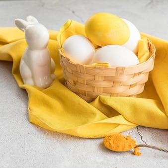 노란색 천에 바구니에 색된 부활절 달걀과 흰색 달걀