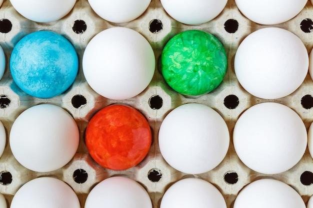 Цветные пасхальные яйца среди белых куриных яиц в картонном подносе