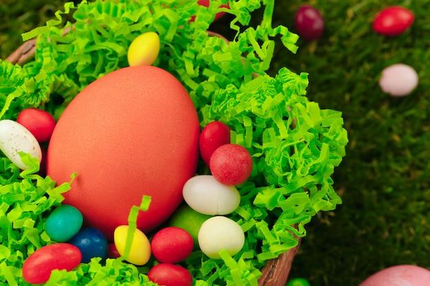 착 색된 부활절 달걀과 사탕 잔디에 프리미엄 사진