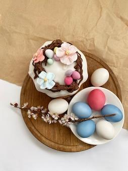 Цветные пасхальные яйца и пасхальный кулич на деревянном столе