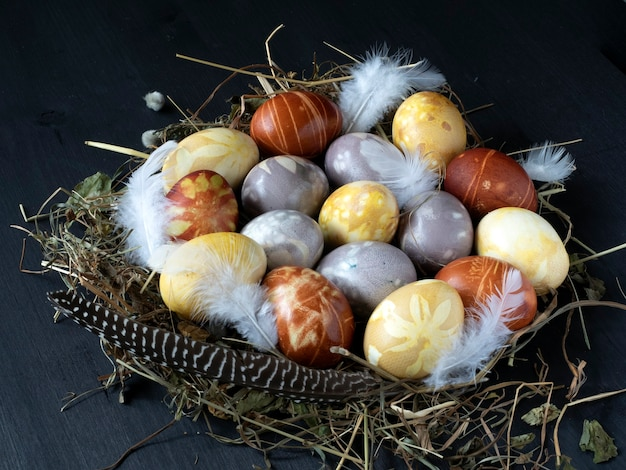 Colored easter eggs are placed on a straw nest and a black wooden table