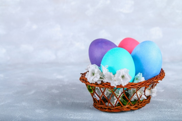 Colored easter eggs in a basket on a gray concrete background.
