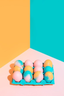 Colored easter eggs in bright rack on pink table