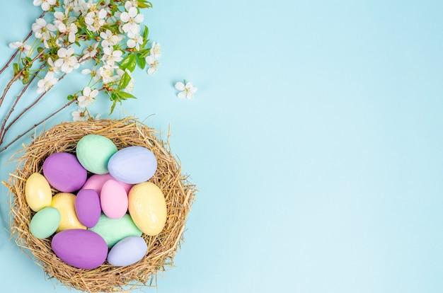青い背景の上の巣の色のイースターエッグ。季節性のコンセプト、春、はがき、休日。フラットレイ、コピースペース、テキスト用のスペース。上から見る