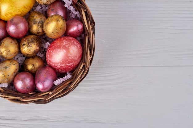 籐のかごの中の着色されたイースターエッグ。コピースペースと上面図の白い木製のテーブルの背景。