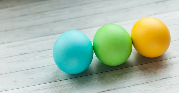 Colored easter eggs on a light wooden background.