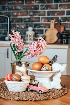 Цветные пасхальные яйца, макаруны, розовые гиацинты и фарфоровые пасхальные кролики на столе в