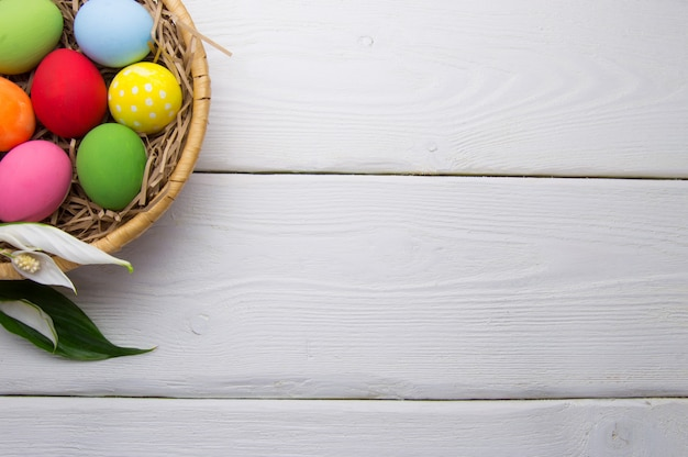 Colored easter eggs on nest beasket with flower on white wooden surface top white