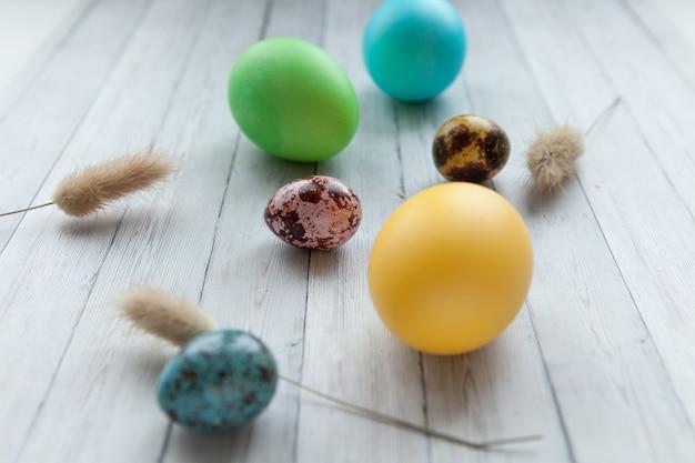 Цветные пасхальные яйца на светлом деревянном фоне. праздник пасхи с крашеными яйцами