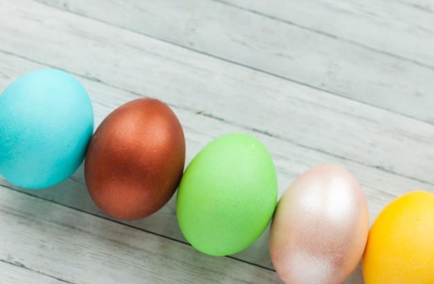 Цветные пасхальные яйца на светлом деревянном фоне.