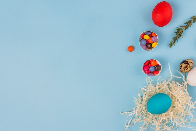 Colored egg in nest with candies on blue table