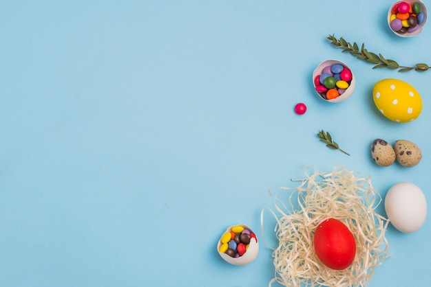 Colored egg in nest with candies on table