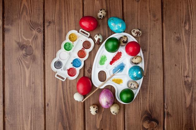 Цветные яйца и краски на деревянном столе, пасхальный фон
