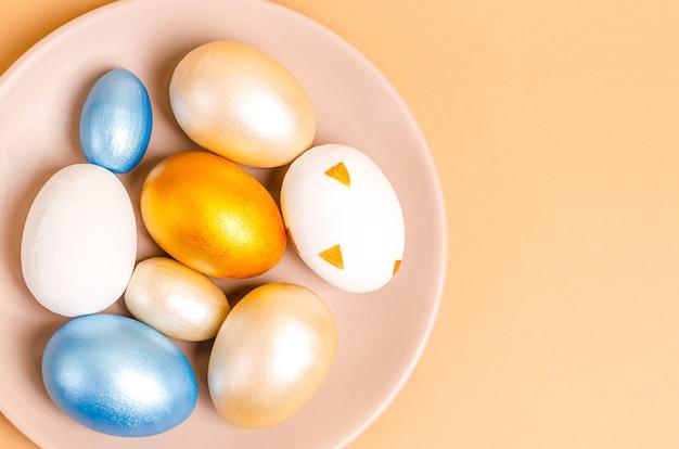 ベージュの背景のおろし金でイースターの色の卵。フラットレイ、ポストカードブランク、テキスト用スペース、コピースペース。上からの眺め。