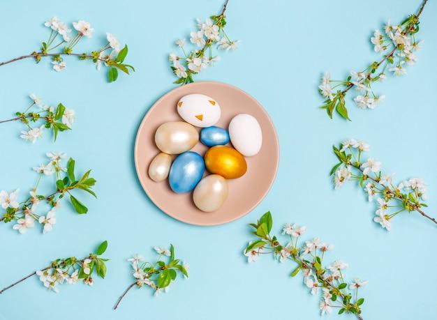 青い背景に開花桜の枝を持つプレート上のイースターの色の卵。フラットレイ、はがき、バナー、コピースペースは空白。上面図
