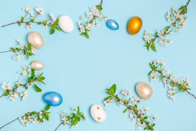 青い背景に開花桜の枝とイースターの色の卵。フラットレイ、はがき、バナー、コピースペースは空白。上面図、