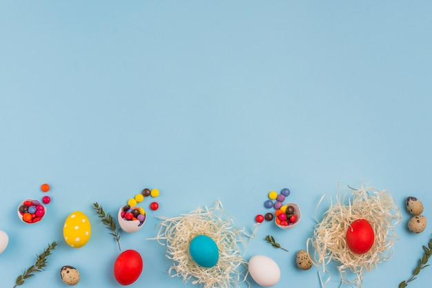 Colored eggs in nests with small candies on table