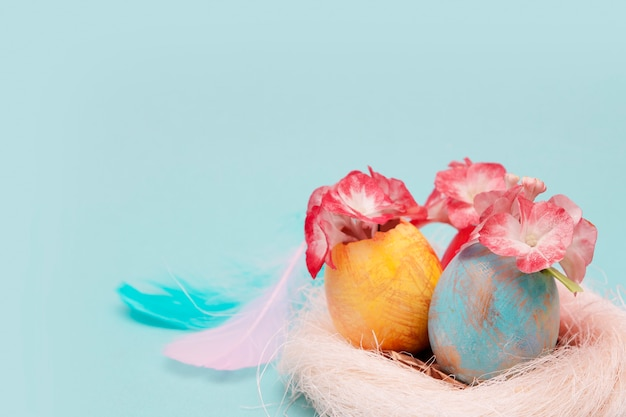 Colored eggs with flowers in a nest on a blue surface