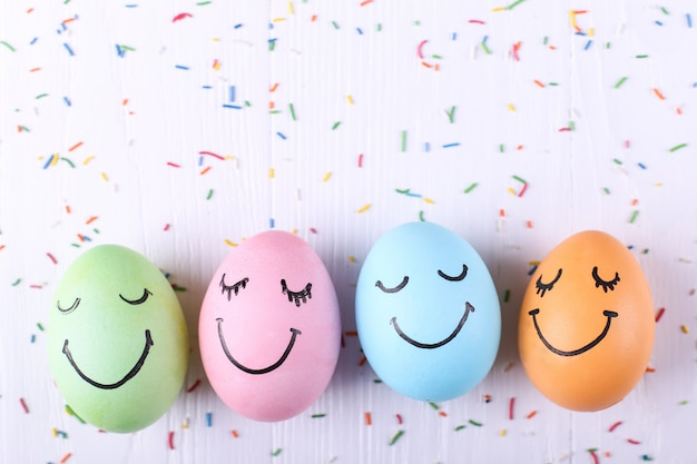 Colored eggs with painted smiles happy easter  greeting card .