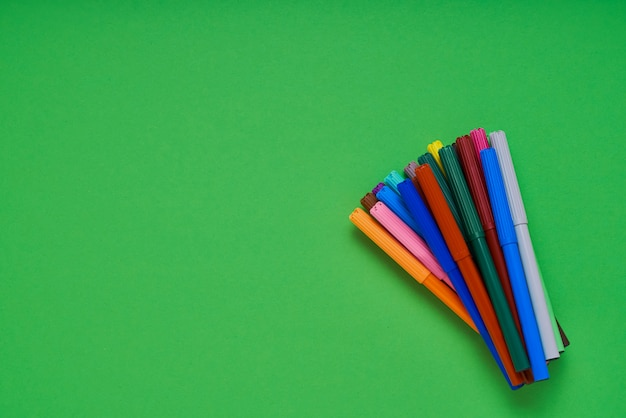 Colored felt tip pens on neon green background with copyspace. top view