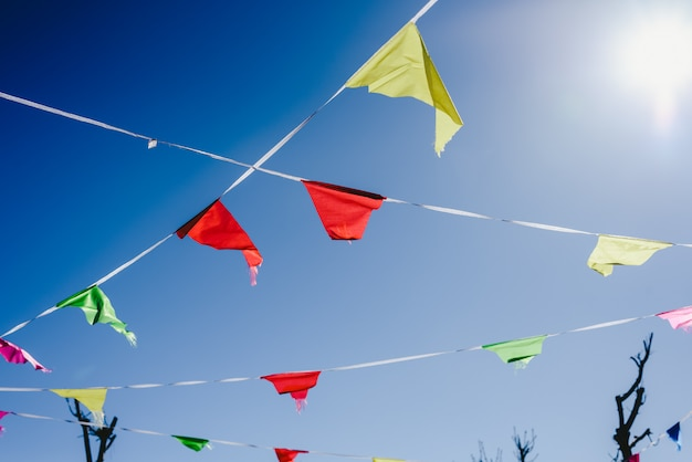 Colored flags against the sun waving in the wind at an outdoor party.