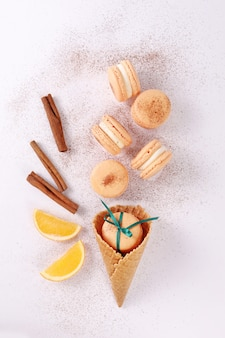 Colored french dessert macarons or macaroons on a white background in the form of ice cream with waffle cone, orange and cinnamon. creative approach.
