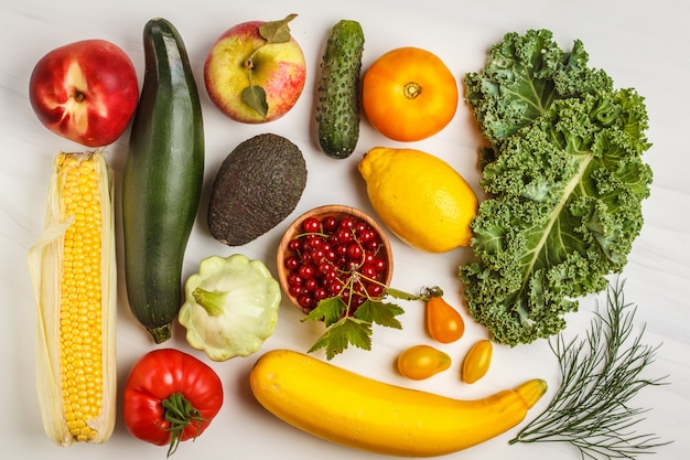 Colored fresh fruits, vegetables and berries on a white background.
