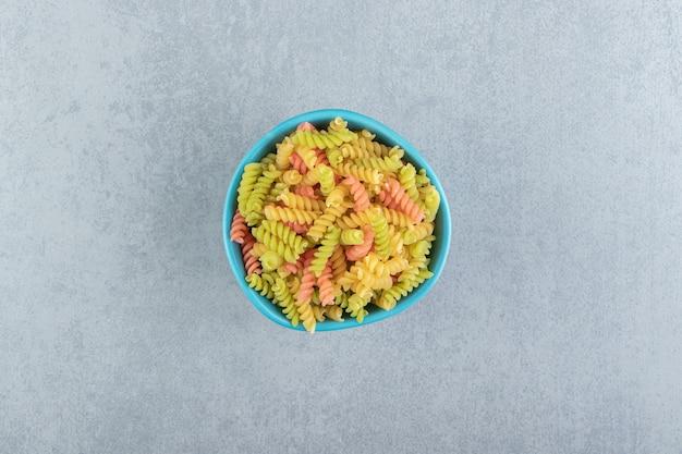 Colored fusilli pasta in blue bowl.