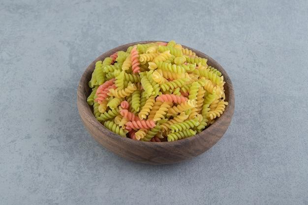 Цветные макаронные изделия фузилли в деревянной миске.