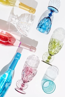 Colored glasses for wine and bottle with champagne sparkling on light with beautiful shadows summer party concept