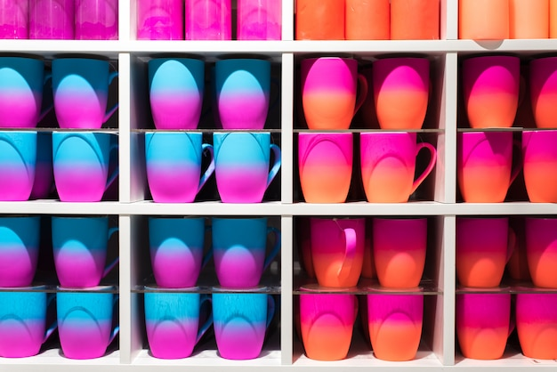 Colored gradient glasses on the shelves in the store. cups of all colors of the rainbow on the counter of the store