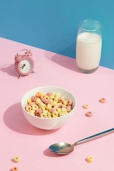분홍색 테이블 어린이 아침 음식에 있는 흰색 그릇에 있는 색깔 있는 곡물 고리