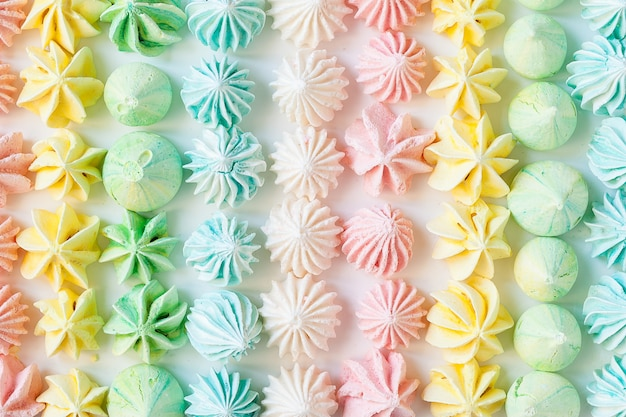 Colored handmade meringues on white backround