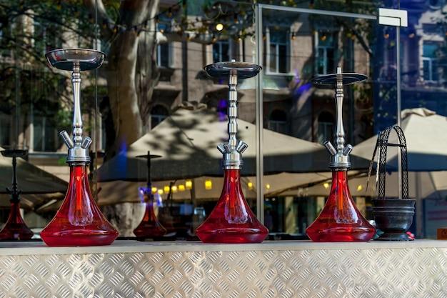 여름날 야외 레스토랑 공간의 배경에 있는 바에 색색의 물담배가 서 있습니다.