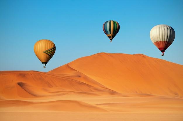 Цветные воздушные шары, летящие над песчаными дюнами на закате. африка, намибия Premium Фотографии