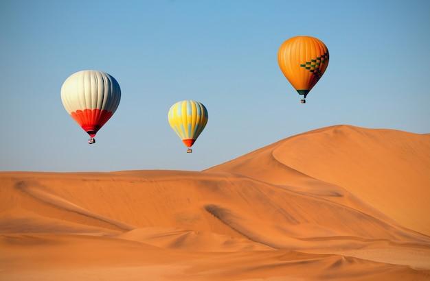 Цветные воздушные шары, летящие над песчаными дюнами на закате. африка, намибия