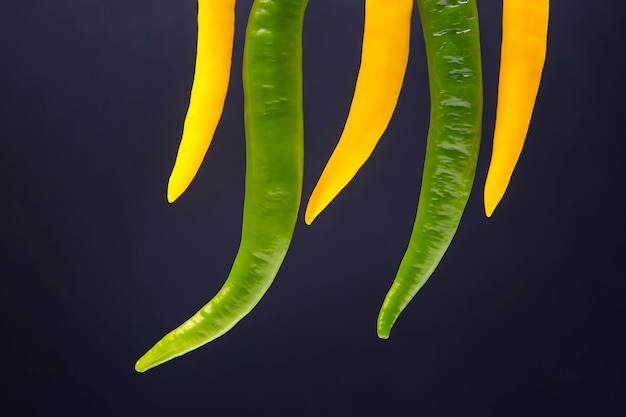 Цветной острый перец чили на темном фоне. перец. растительное витаминное питание.