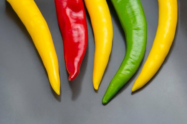 Цветной острый перец чили на сером. перец. растительное витаминное питание.