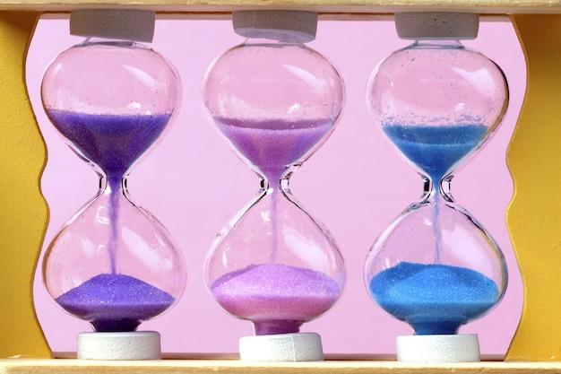 Цветные песочные часы на розовом фоне стены
