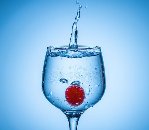 色付きの氷球がカクテルグラスに落ちて水しぶきを上げた。