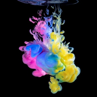Colored inks in water on black surface Premium Photo
