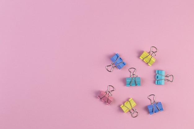 Colored iron paper clips on a pink wall, binder clip is a simple device for binding sheets of paper together, metal clips in chaos. office supplies. space for text.