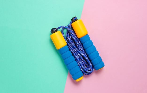 Цветные прыжки через скакалку на розово-голубом пастельном фоне. концепция спорта минимализм.