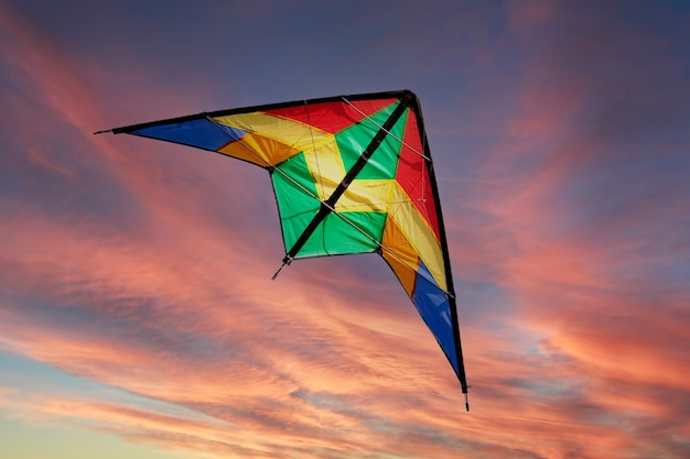 Colored kite flying in the middle of a beaurtiful sunset